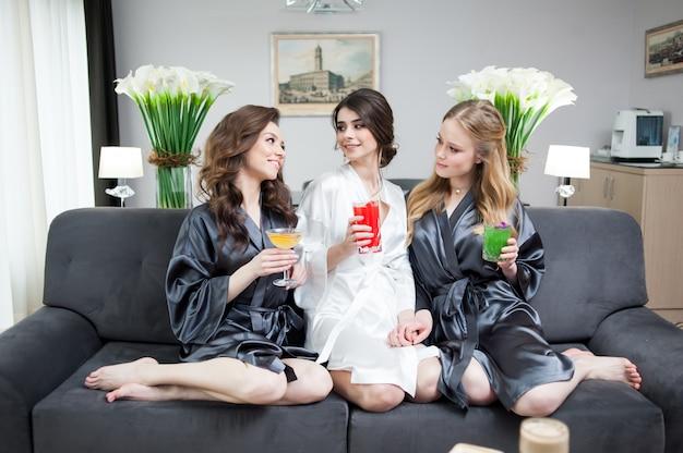 Schöne braut mit brautjungfer, die champagner vor der hochzeit trinkt. morgenbraut.