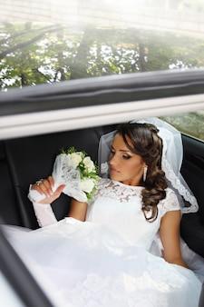 Schöne braut mit einem strauß von rosen, die im auto sitzen