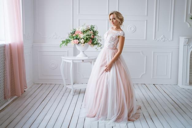Schöne braut mit haaren und make-up steht in zarten rosa hochzeitskleid in einem hellen dekor mit blumen
