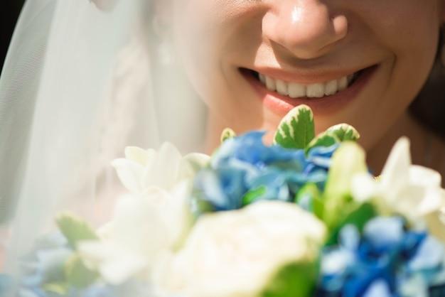Schöne braut mit hochzeitsblumenstrauß, attraktive frau im hochzeitskleid. glückliche frisch verheiratete frau. braut mit hochzeits make-up und frisur. lächelnde braut. hochzeitstag. ehe.