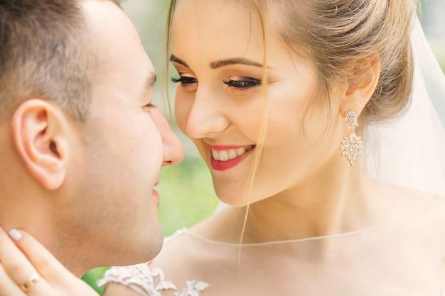 Schöne braut mit sanftem make-up schaut auf den bräutigam und will küssen. nahansicht.