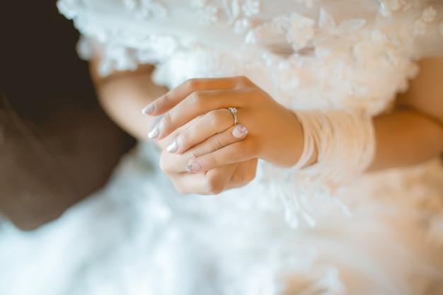 Schöne braut mit weißem hochzeitskleid halten ihren ehering im glatten gefühl.