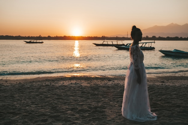 Schöne braut posiert am strand hinter dem meer bei sonnenuntergang