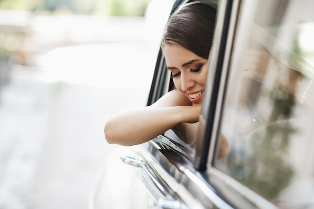 Schöne braut sitzt mit hochzeitsblumenstrauß in einem retro- auto und hat spaß