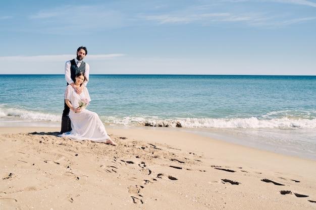 Schöne braut und bräutigam am strand schauen sich mit viel liebe und freude an