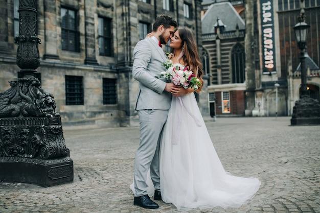 Schöne braut und bräutigam, die an ihrem hochzeitstag im freien umarmen und küssen