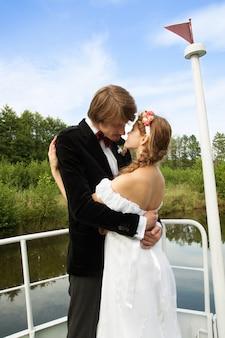 Schöne braut und bräutigam, die auf einem schiff küsst