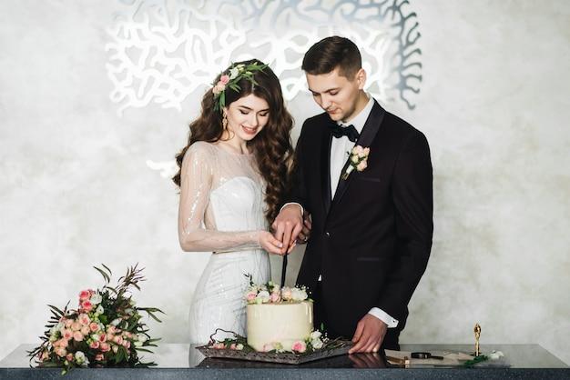 Schöne braut und bräutigam, die einen wunsch machen, während sie stehen, die hochzeitstorte zusammen schneiden