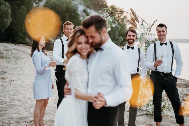 Schöne braut und bräutigam, die ihre hochzeit mit gästen am strand haben