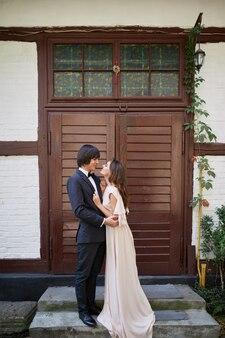 Schöne braut und bräutigam, die nahe beieinander am alten haushintergrund, hochzeitsfoto, schönes paar, hochzeitstag, porträt stehen.