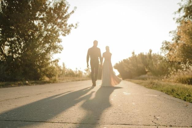 Schöne braut und bräutigam gehen gegen die sonne. zwei liebende umarmen und küssen sich