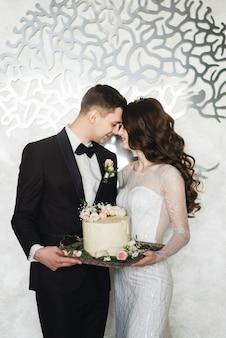 Schöne braut und bräutigam machen einen wunsch, wie sie mit der hochzeitstorte zusammen stehen
