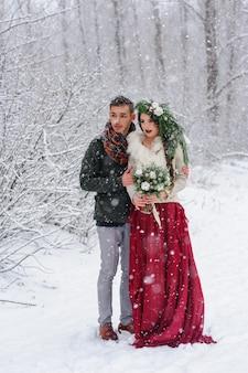 Schöne braut und bräutigam mit einem weißen hund stehen auf der landschaft eines verschneiten waldes.