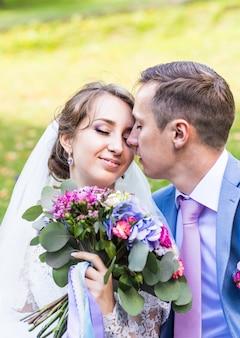 Schöne braut und bräutigam umarmen sich an ihrem hochzeitstag im freien