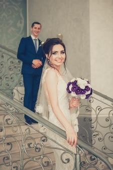 Schöne braut und hübscher bräutigam auf treppen