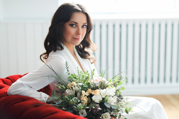Schöne brautfrau im eleganten hochzeitskleid mit blumenstrauß