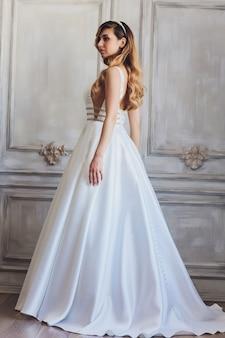 Schöne brautfrau im hochzeitskleid und im schleier. modeporträt der jungen wunderschönen braut. hochzeitskleid.