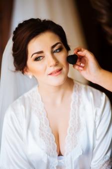 Schöne brauthochzeit mit make-up und lockiger frisur. stylist macht make-up braut am hochzeitstag. schönheitsporträt der jungen frau am morgen.