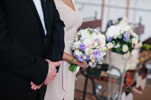 Schöne brautjungfer, die einen hochzeitsblumenstrauß in der kirche hält.