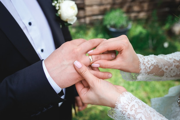 Schöne brautmädchen im weißen hochzeitskleid legt auf den finger des bräutigams den hochzeitsgoldring