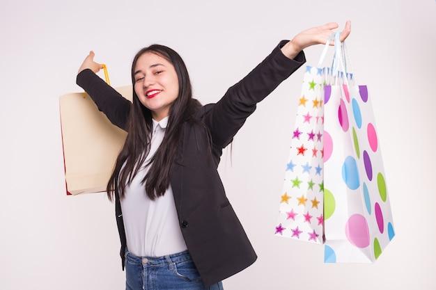 Schöne brünette asiatische frau mit den roten lippen, die einkaufstaschen in weiß erheben.