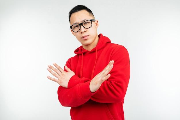 Schöne brünette asiatische in rotem sweatshirt und brille für vision winken seine hände auf einem weißen hintergrund.
