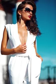 Schöne brünette auf der straße trägt weißen pullover