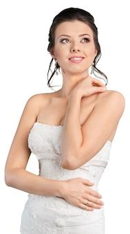 Schöne brünette braut im weißen hochzeitskleid auf weißem hintergrund