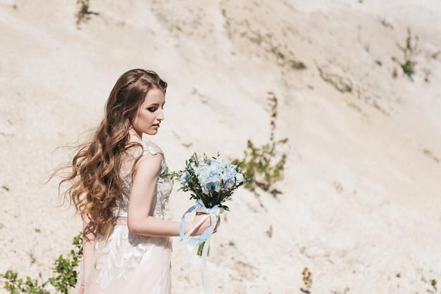 Schöne brünette braut mit fliegenden locken auf dem hintergrund eines sandigen berges in einem stilvollen kleid und einem blauen und weißen blumenstrauß.