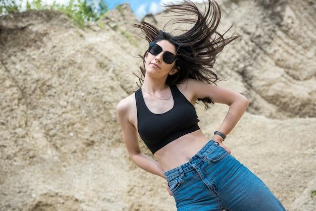 Schöne brünette dame im sandsteinbruch entspannen und genießen sie ihre zeit am sonnigen sommertag