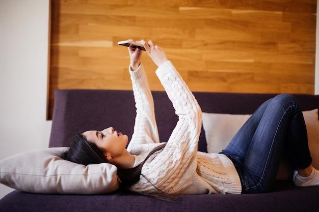 Schöne brünette, die ein selfie mit ihrem smartphone zu hause am weißen kissen nimmt