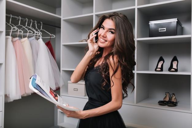 Schöne brünette, die telefonisch im ankleidezimmer und im lesemagazin spricht. beschäftigtes leben der stilvollen frau. sie hat lange schöne haare und trägt ein schwarzes schönes kleid.
