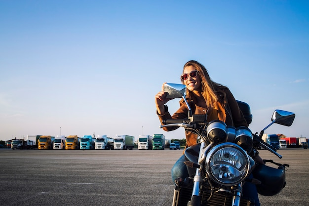 Schöne brünette frau, die auf retro-artmotorrad sitzt und sich in den spiegeln schaut