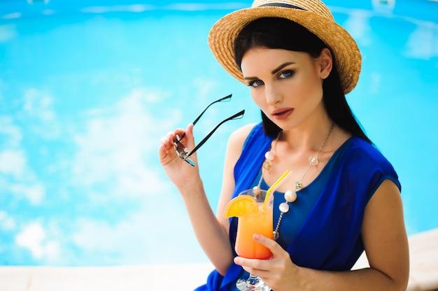 Schöne brünette frau, die einen blauen bikini trägt und den pool genießt, sommerzeit.
