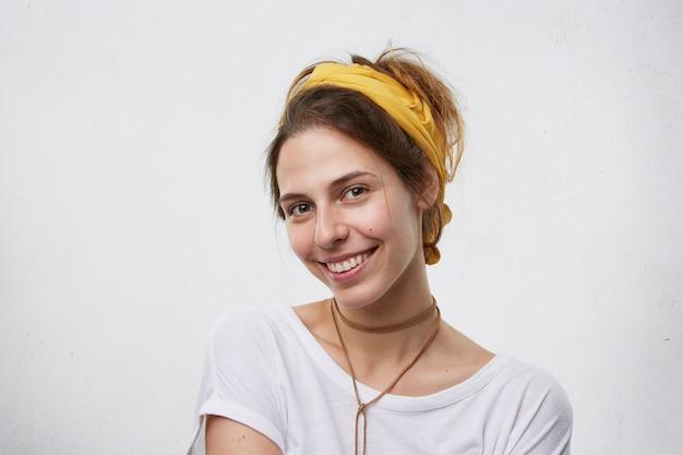 Schöne brünette frau, die gelben schal auf kopf, anhänger am hals und weißes t-shirt trägt, das angenehm lächelnd augen des glücks trägt. nettes weibchen lokalisiert über leere weiße wand