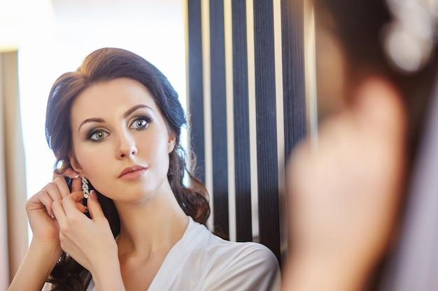 Schöne brünette frau, die in der nähe des spiegels steht und ohrringe anzieht