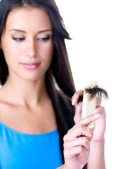 Schöne brünette frau, die kämmt und auf die enden ihres langen haares schaut - vordergrund