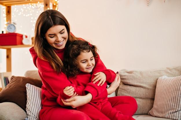 Schöne brünette frau, die kind mit lächeln umarmt. junge mutter in roter kleidung, die auf couch mit kleiner tochter sitzt.