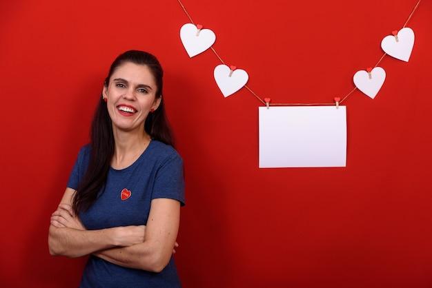 Schöne brünette frau, die lässiges blaues t-shirt über isoliertem rotem hintergrund trägt, der nahe rechteckigem banner und weißen herzen lächelt