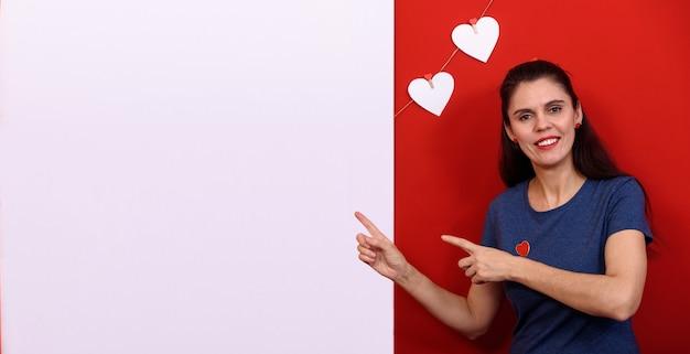 Schöne brünette frau, die lässiges blaues t-shirt über lokalisiertem rotem hintergrund trägt, der nahe rechteckigem banner und weißen herzen lächelt und auf dieses zeigt. speicherplatz kopieren