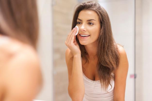 Schöne brünette frau, die make-up von ihrem gesicht entfernt