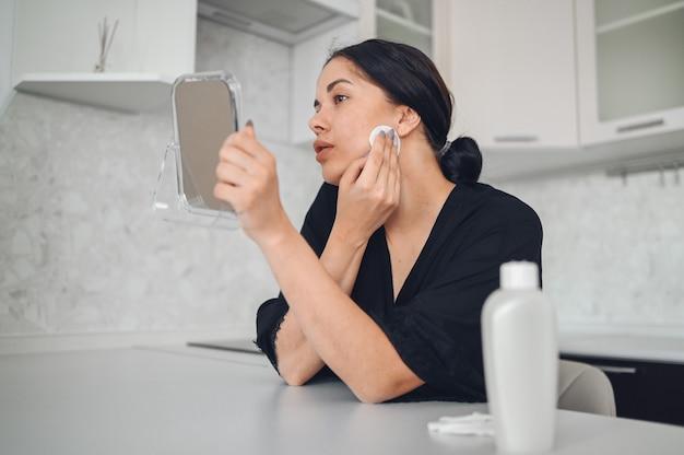Schöne brünette frau, die make-up von ihrem gesicht mit spiegel entfernt. nettes schönes natürliches schönheitsmädchen, das gesicht mit baumwollschwamm reinigt. kosmetologie und spa, problemhautpflege, aknebehandlungskonzept