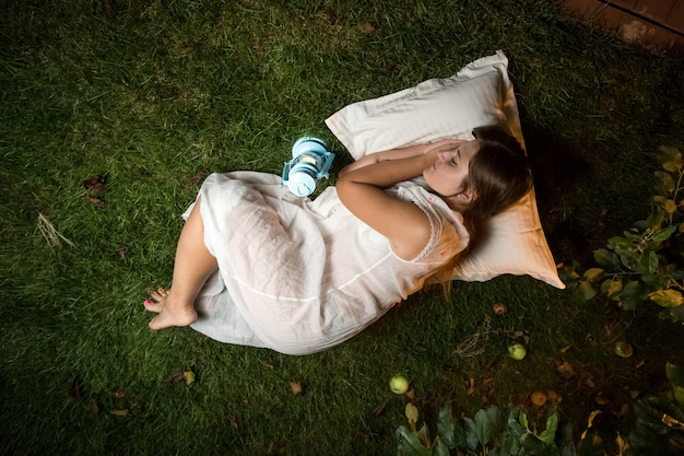 Schöne brünette frau, die nachts im garten auf kissen schläft