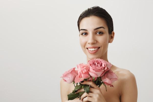Schöne brünette frau, die nackt mit rosenstrauß steht