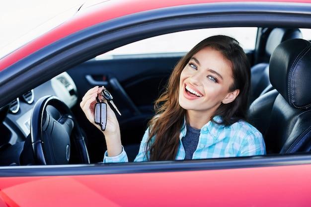 Schöne brünette frau, die rotes auto fährt und auto kauft. glücklicher besitzer des neuen autos, kamera betrachtend und lächelnd, schlüssel haltend. kopf und schultern, glücklicher fahrer
