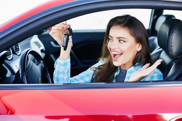 Schöne brünette frau, die rotes auto fährt und auto kauft. glücklicher besitzer des neuen autos, schlüssel vom auto betrachtend und lächelnd. kopf und schultern, glücklicher fahrer