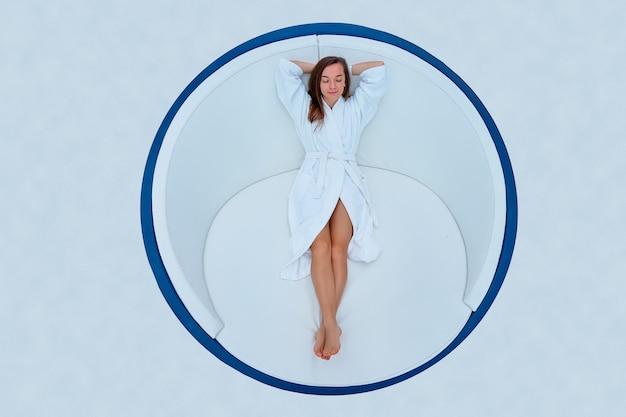 Schöne brünette frau, die weißen bademantel mit geschlossenen augen und händen hinter kopf trägt, der auf einer liege liegt und entspannende zeit genießt und sich in einem wellness-spa-resort gut fühlt
