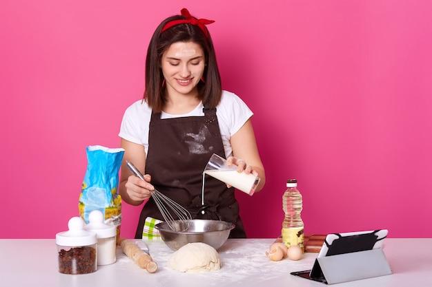 Schöne brünette frau gießt milch in platte. chefkoch knetet teig, bereitet sich auf die osterferien vor und macht heiße brötchen. rosa wand. konzept des kochens von lebensmitteln und backen von kuchen. speicherplatz kopieren.