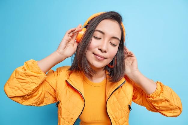 Schöne brünette frau hat augen geschlossen trägt drahtlose kopfhörer hört musik kippt den kopf in orangefarbener jacke, isoliert über blauer wand. menschen lifestyle-hobby-konzept