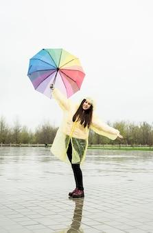 Schöne brünette frau im gelben regenmantel mit regenbogenregenschirm im regen
